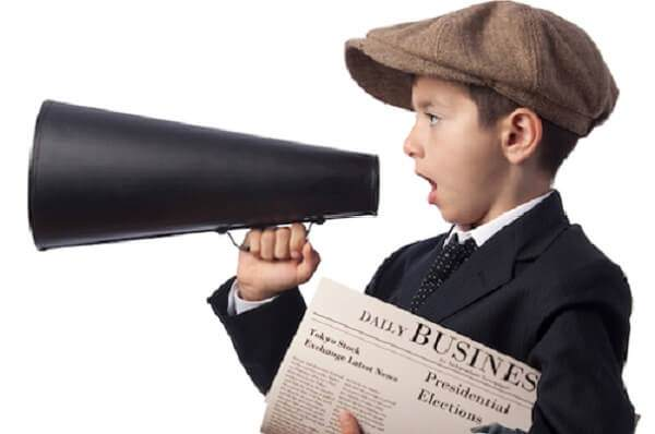 Stock photo of a newsie holding a newspaper and megaphone.